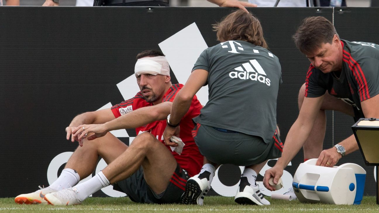 Bayern Munich's Franck Ribery is treated by medical staff after colliding with a goalpost.