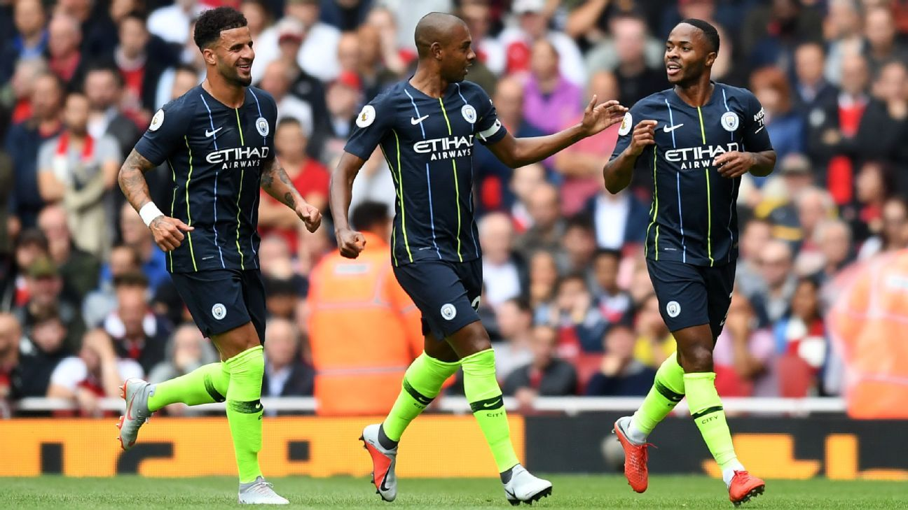 Raheem Sterling of Manchester City (R) celebrates after scoring at Arsenal.