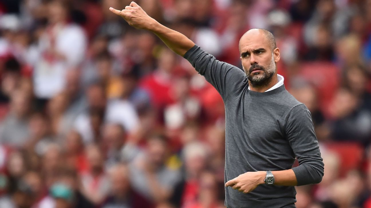 Pep Guardiola gestures on the touchline at Arsenal.