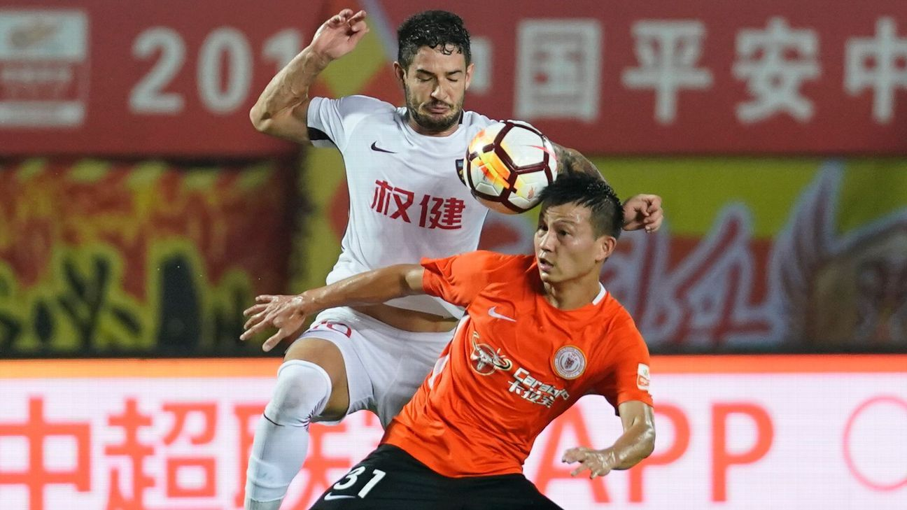 Tianjin Quanjian's Alexandre Pato, left, battles for possession with Beijing Renhe's Rao Weihui.