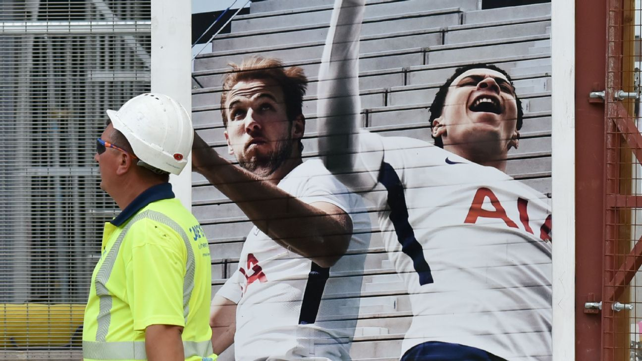A construction worker walks by a mural of Harry Kane and Dele Alli outside the new Tottenham Hotspur stadium.