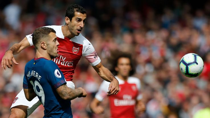 Henrikh Mkhitaryan challenges for the ball with Jack Wilshere.