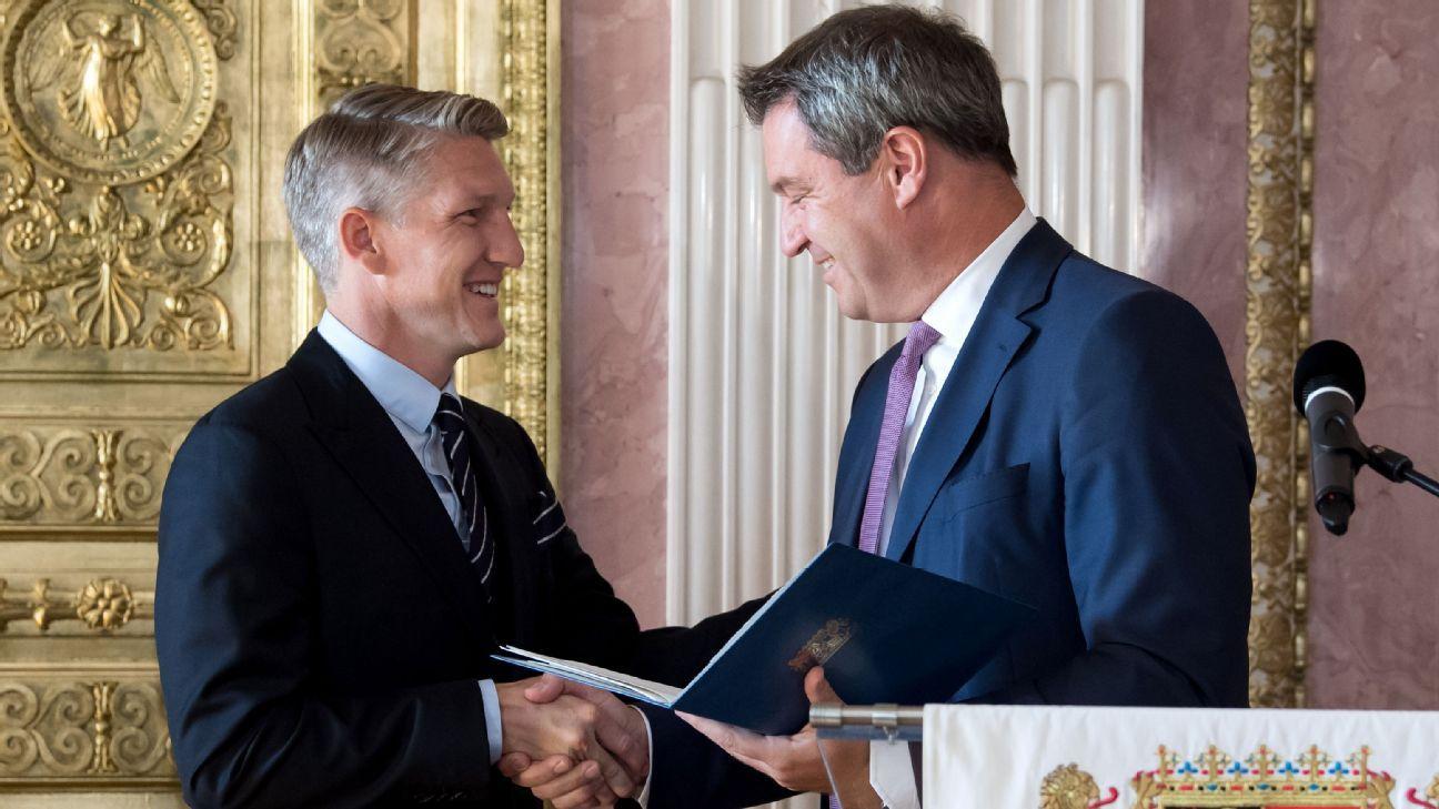 The Chicago Fire's Bastian Schweinsteiger, left, receives the Bavarian Order of Merit from Markus Soder.