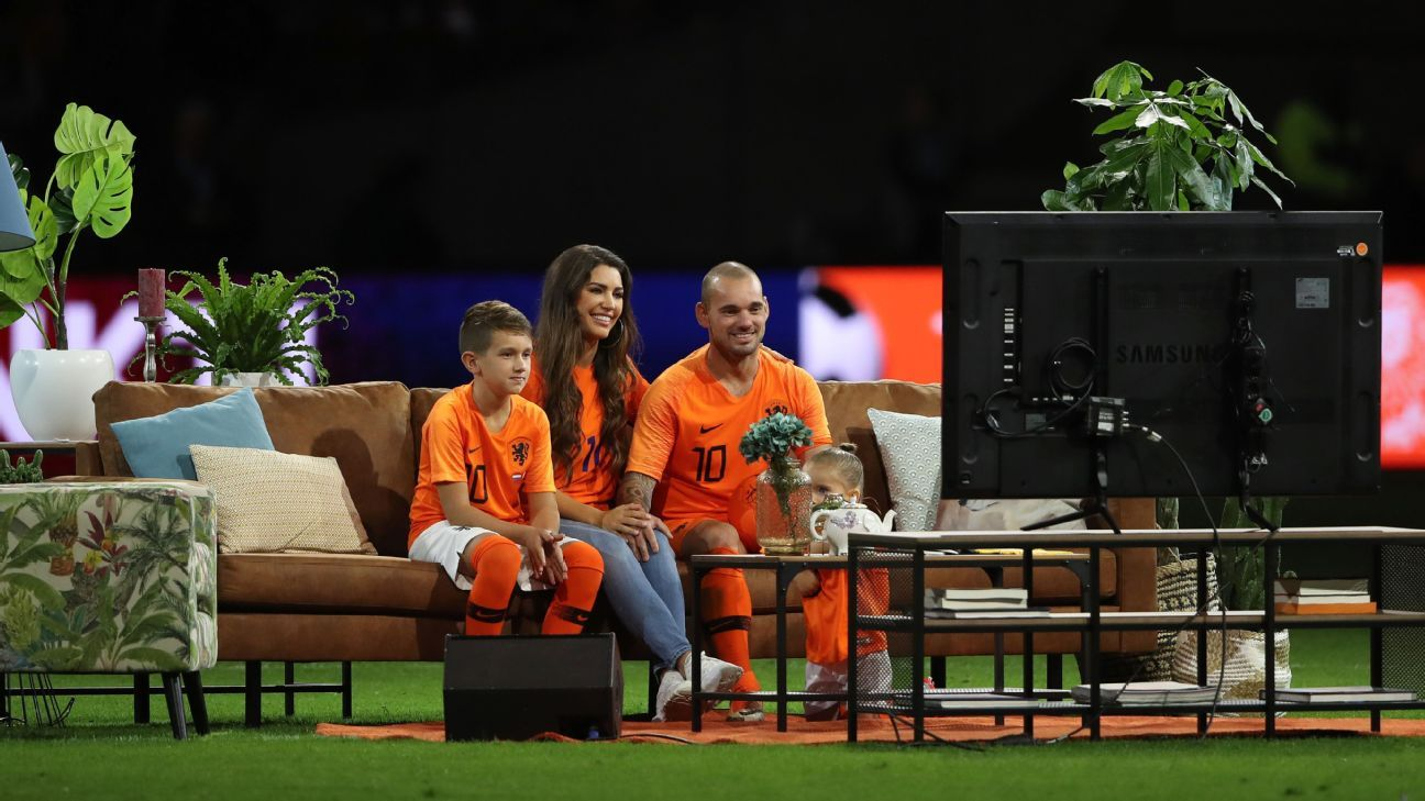 Wesley Sneijder sits on a sofa and watches TV highlights with his family on the pitch.