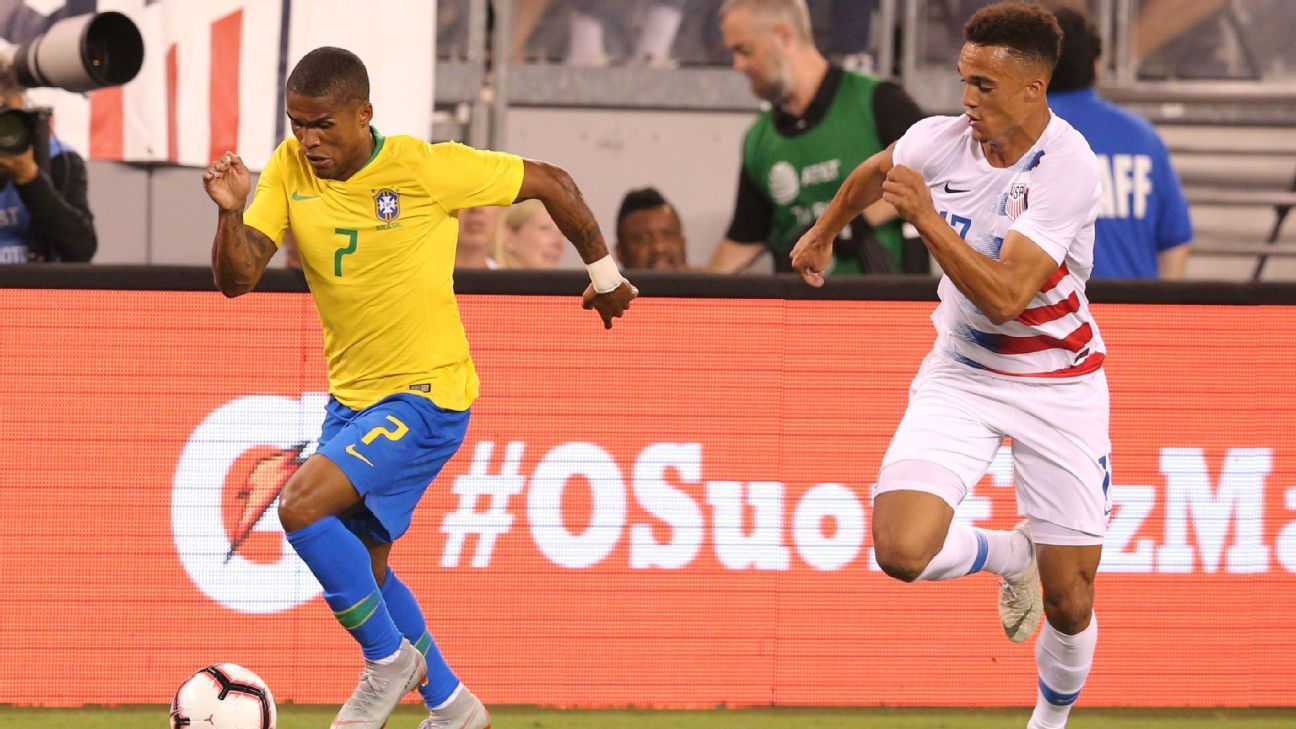 Antonee Robinson, right, chases down Douglas Costa during a friendly between the United States and Brazil.