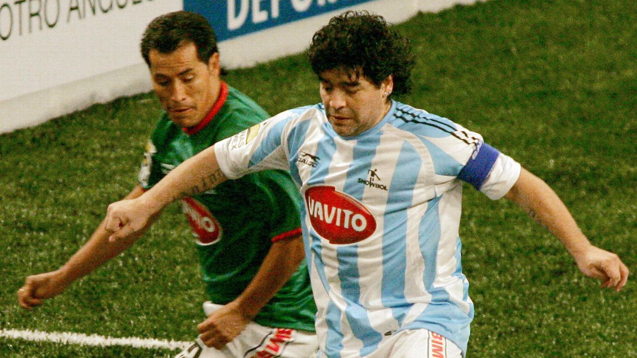 Diego Maradona shields the ball from Benjamin Galinfo during a 'Showbol' event in Mexico City in 2006
