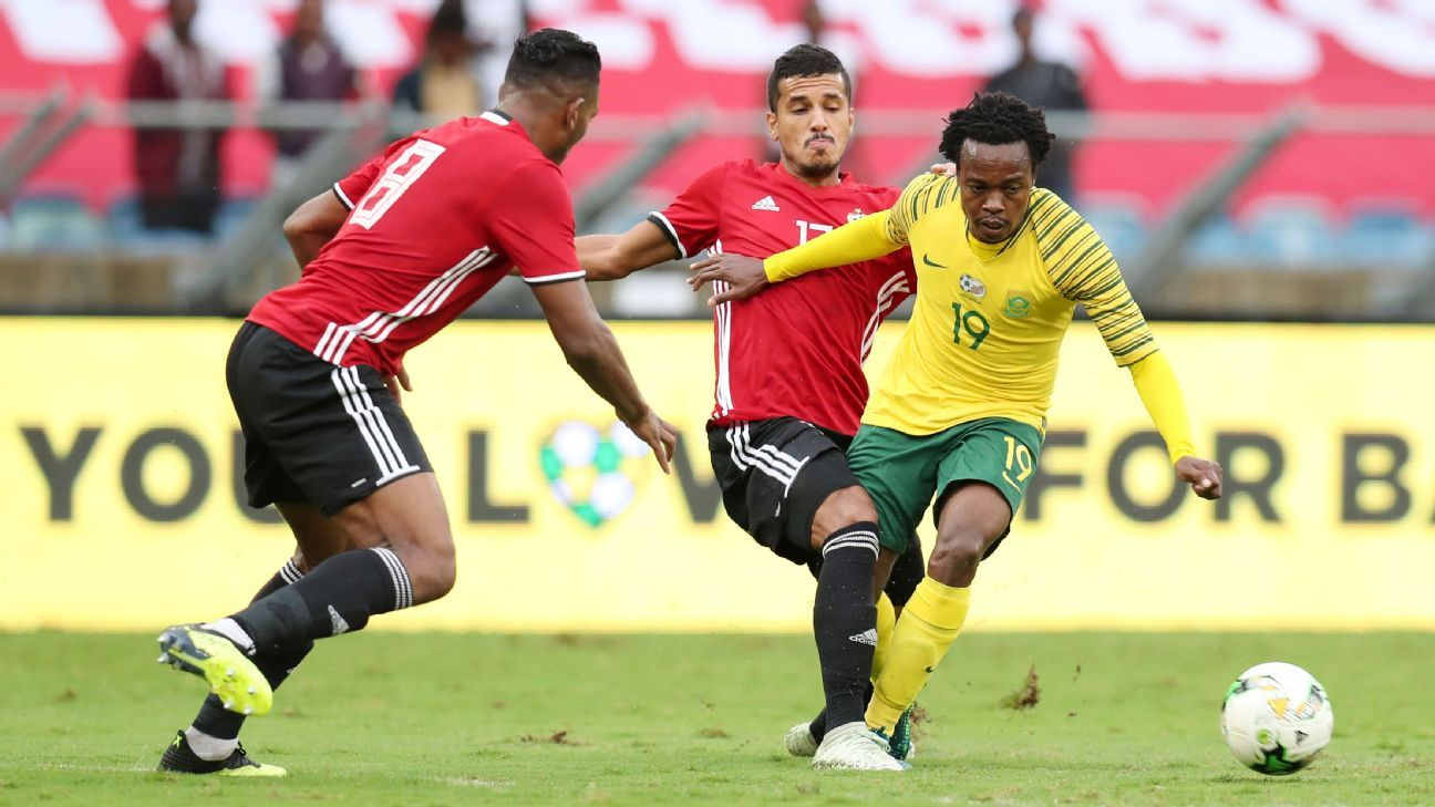 Percy Tau of South Africa is challenged by Ismaiel Sharadi and Sand Masaud of Libya