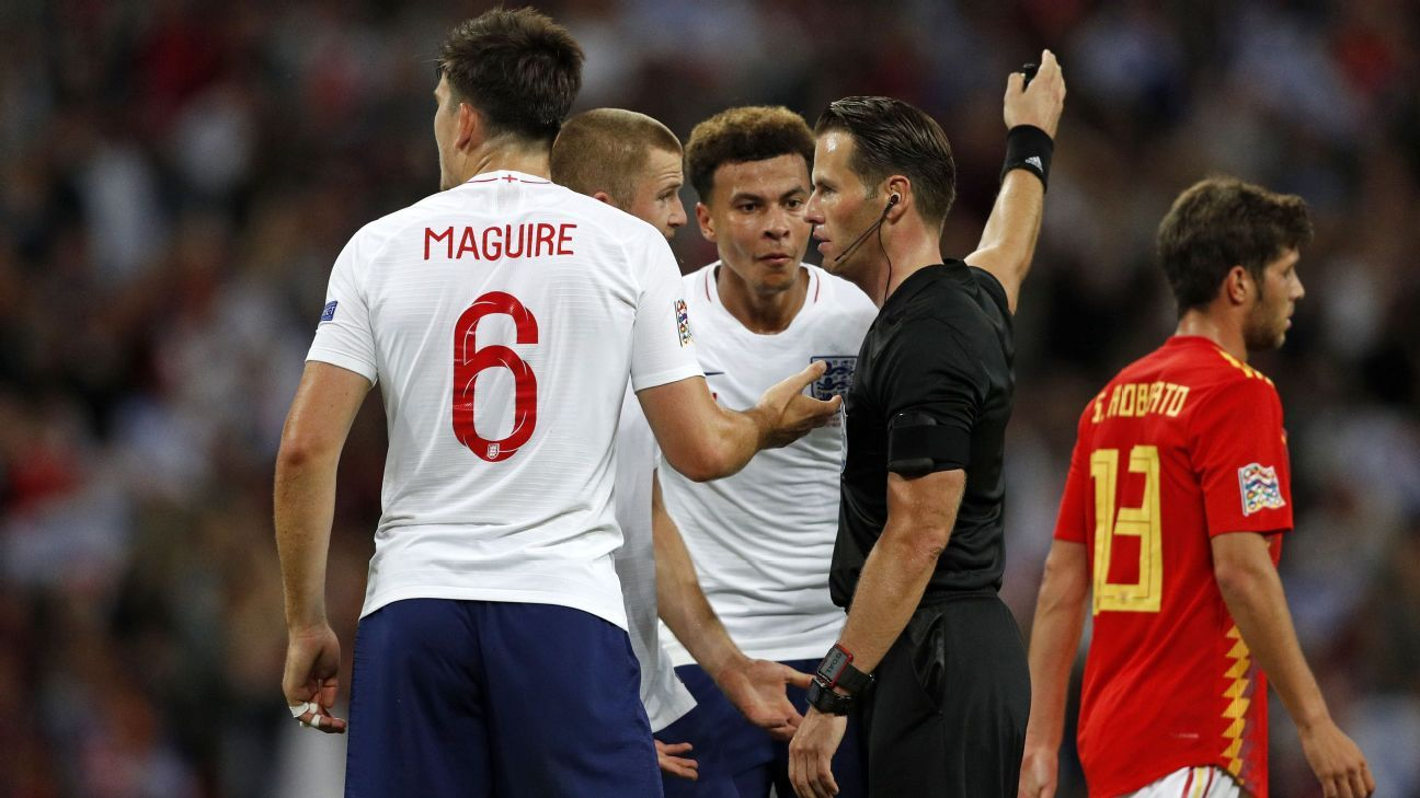 Dele Alli and Eric Dier speak to referee Danny Makkelie after he disallowed a late goal by Danny Welbeck.