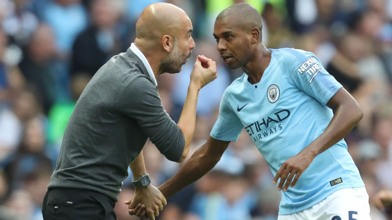 Pep Guardiola speaks with Manchester City's Brazilian midfielder Fernandinho.