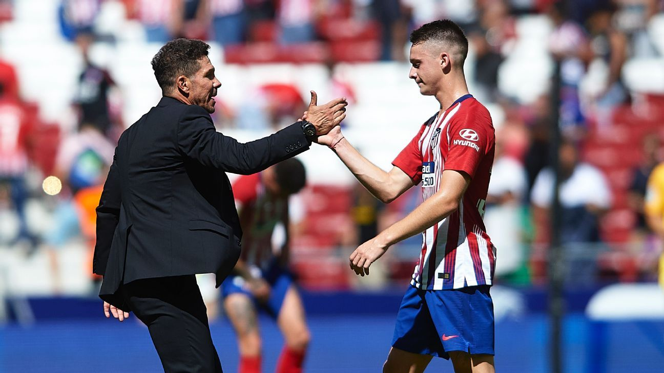 Atletico Madrid coach Diego Simeone, left, shakes hands with Borja Garces.