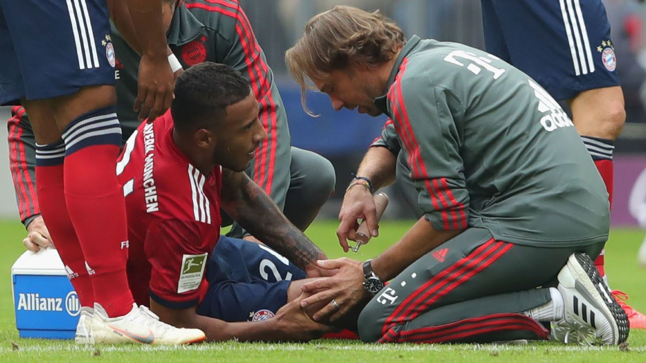 Bayern Munich's Corentin Tolisso receives treatment from Peter Ueblacker.