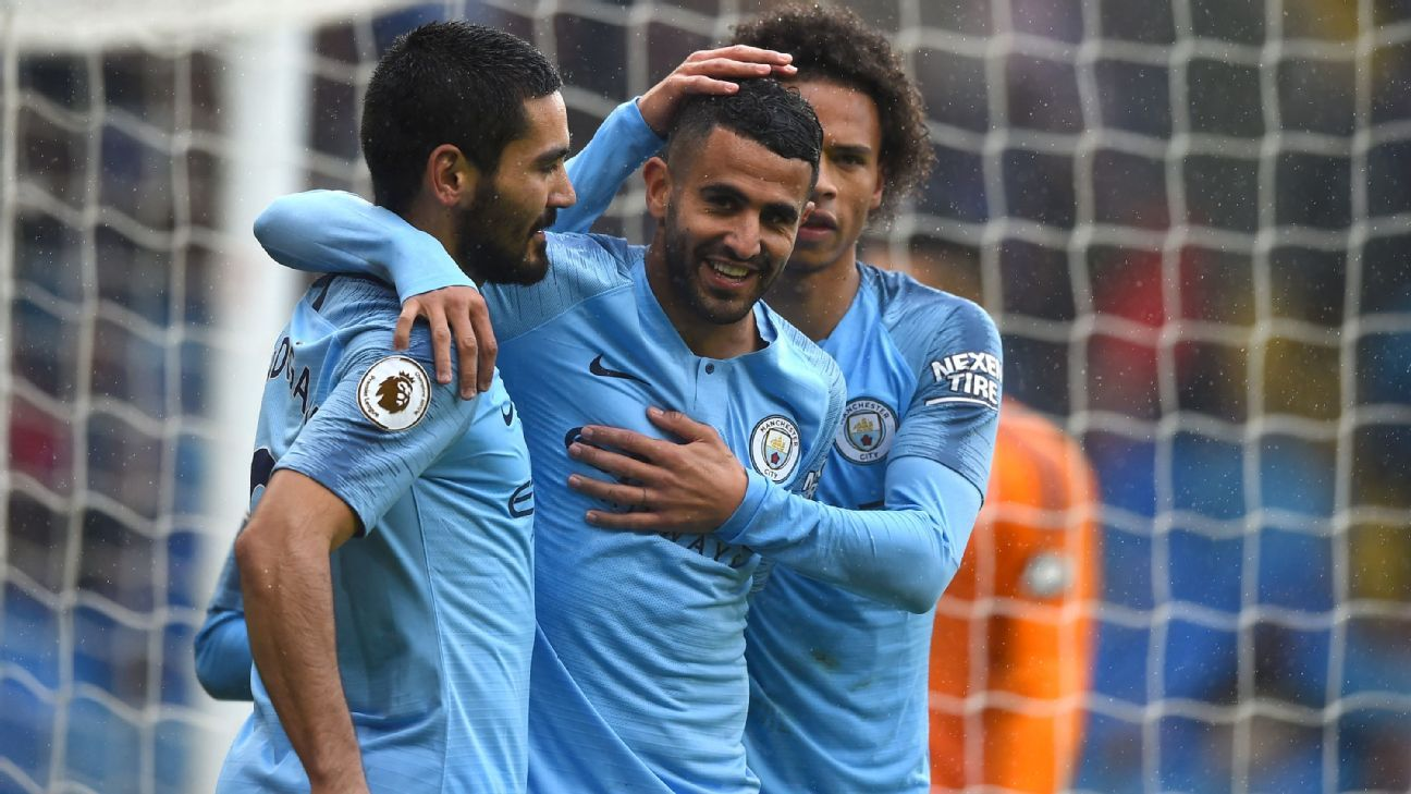 Manchester City players celebrate after scoring a fourth against Cardiff