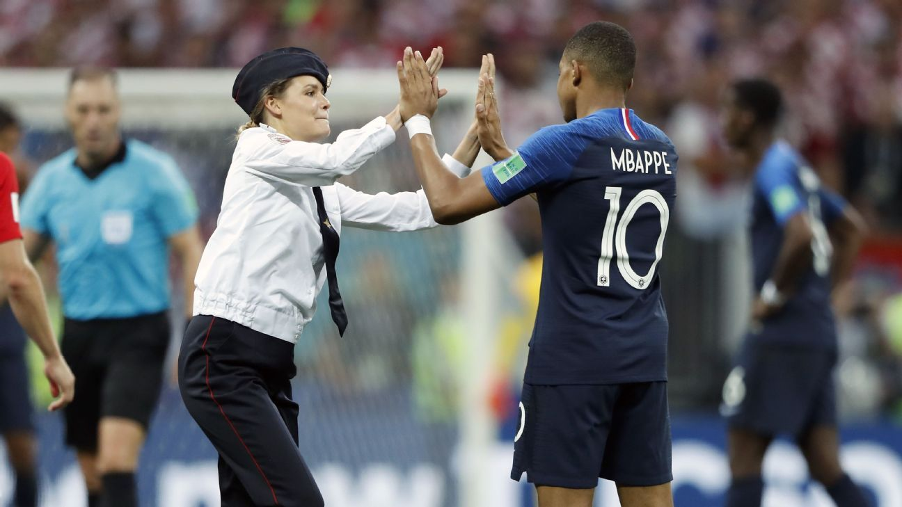 A member of Pussy Riot is doing a high five with France's Kylian Mbappe during the World Cup final.