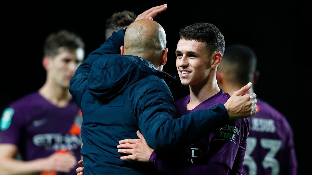 Phil Foden, right, is congratulated by his Manchester City manager Pep Guardiola after a win in the Carabao Cup.