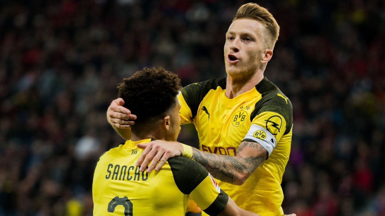 Dortmund's Marco Reus, right, celebrates with teammate Jadon Sancho after scoring a goal against Bayer Leverkusen.