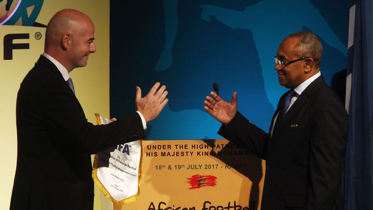 FIFA President Gianni Infantino (L) shakes hands with president of the African Football Confederation (CAF) Ahmad Ahmad during the African Football Symposium in 2017