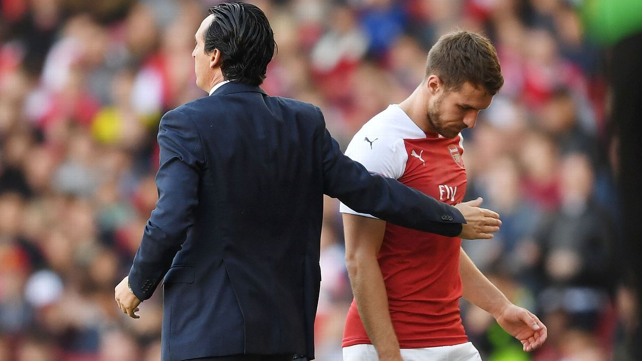 Aaron Ramsey walks past Arsenal head coach Unai Emery after his substitution.