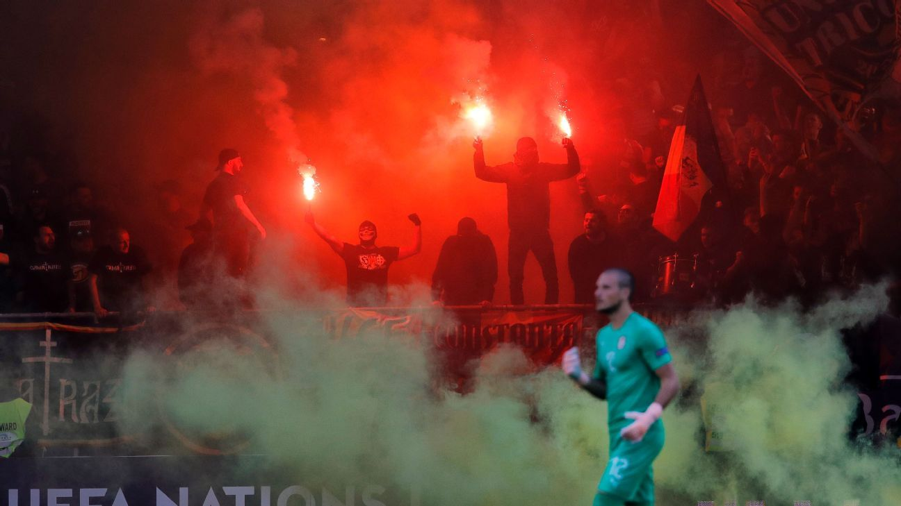 Serbia's goalkeeper Predrag Rajkovic walks off the pitch as Romania fans light flares during a UEFA Nations League match on Sunday.