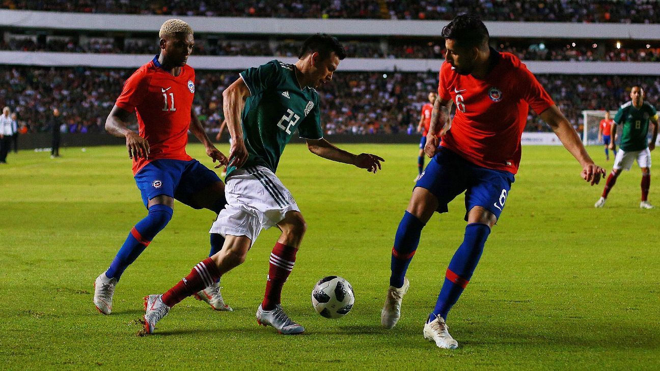 Hirving Lozano of Mexico holds off Chile's Junior Fernandez and Guillermo Maripan.