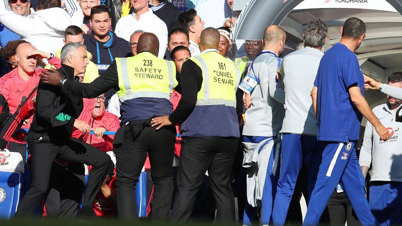 Stewards hold back Jose Mourinho as he clashes with a member of the Chelsea backroom staff.