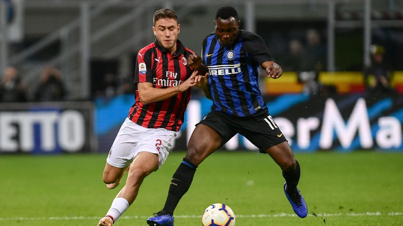 Davide Calabria and Kwadwo Asamoah vie for the ball during AC Milan's Serie A match against Inter.