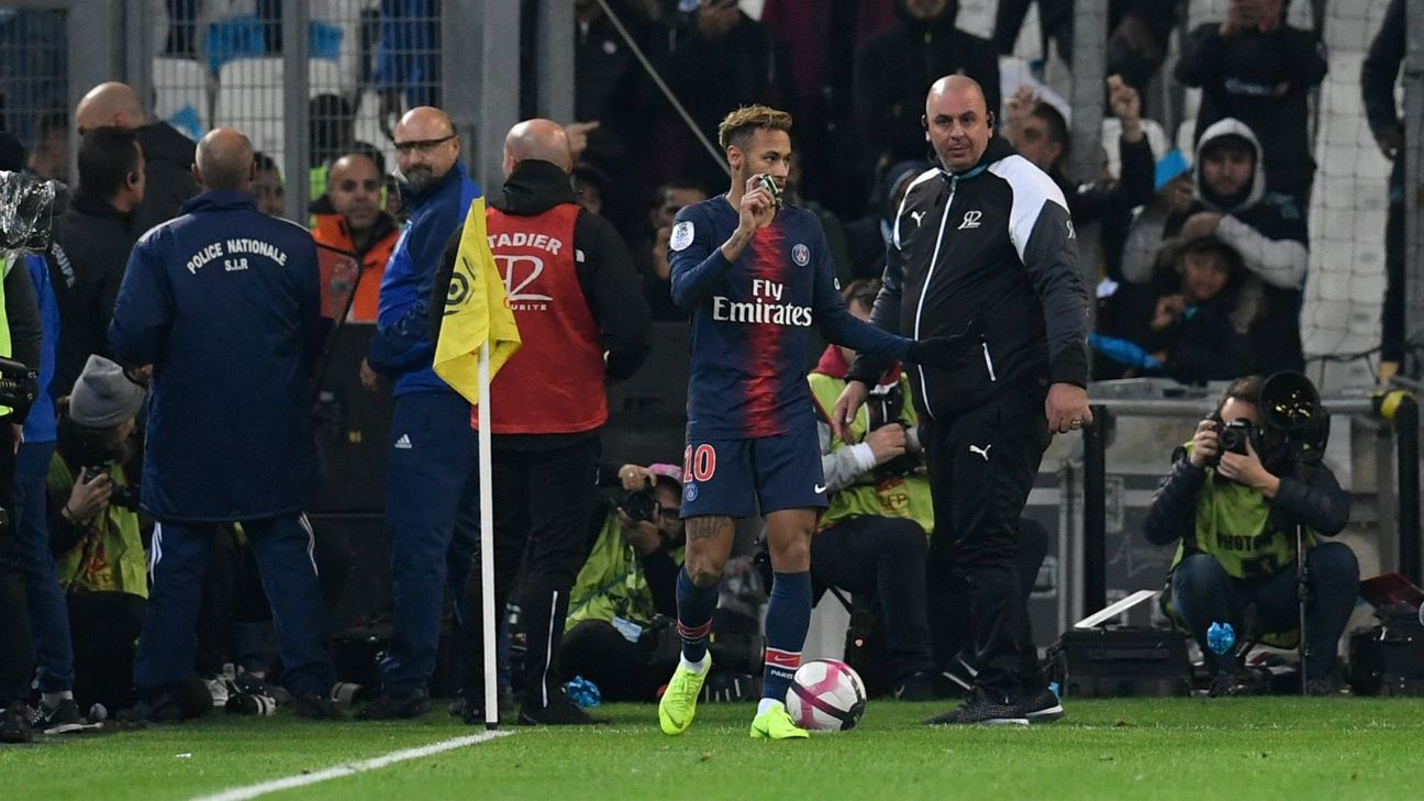 Paris Saint-Germain's Neymar, centre, holds up an object thrown by Marseille supporters.