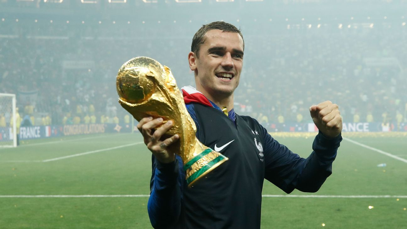 France's Antoine Griezmann celebrates with the World Cup trophy.