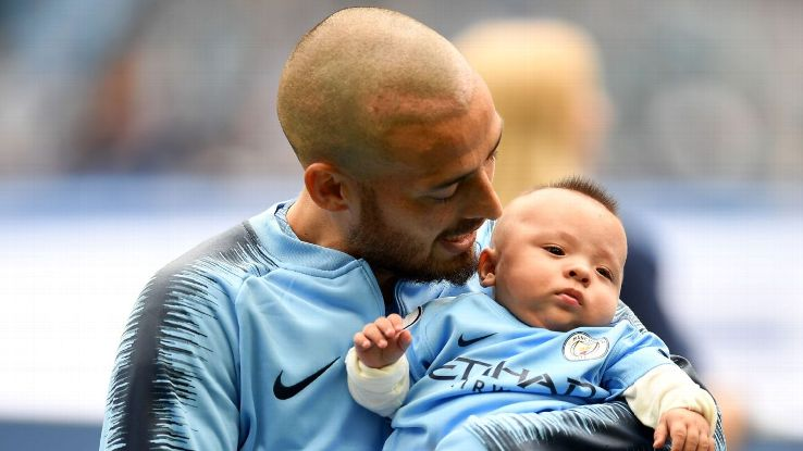David Silva hold his son Mateo as the teams line up prior to the Premier League match between Manchester City and Huddersfield Town.