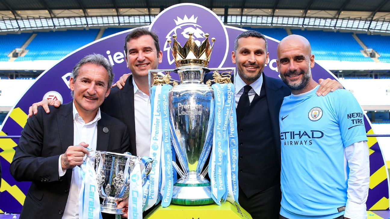 Manchester City directors pose with the Premier League trophy.