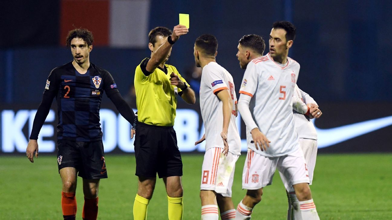 Referee Aleksei Kulbakov gives a yellow card to Spain's Dani Ceballos during their Nations League match against Croatia.