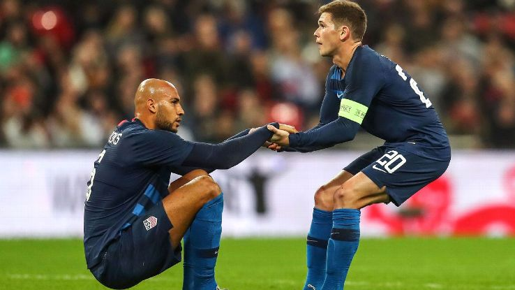 Wil Trapp helps John Brooks up during the U.S.'s friendly loss to England.