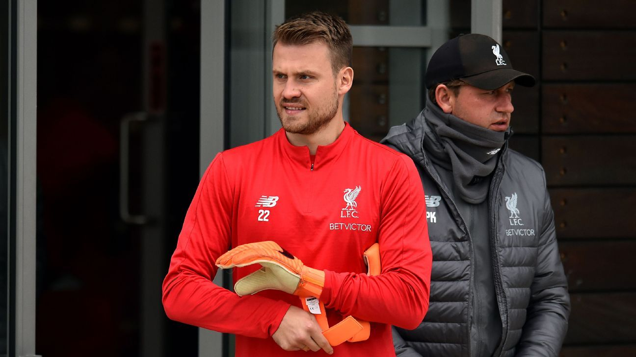 Liverpool goalkeeper Simon Mignolet walks out onto the training pitch at Melwood