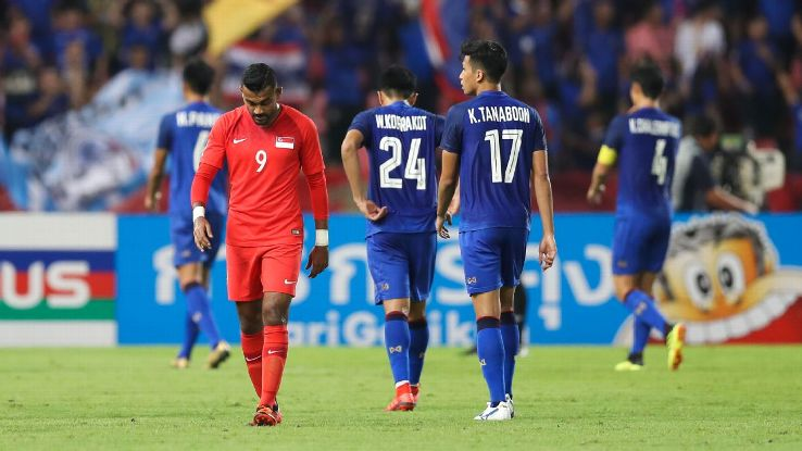 Singapore's Faritz Hameed shows his dejection as Thailand players celebrate in the background