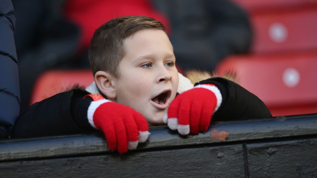 A young Manchester United fan yawns in the stands.