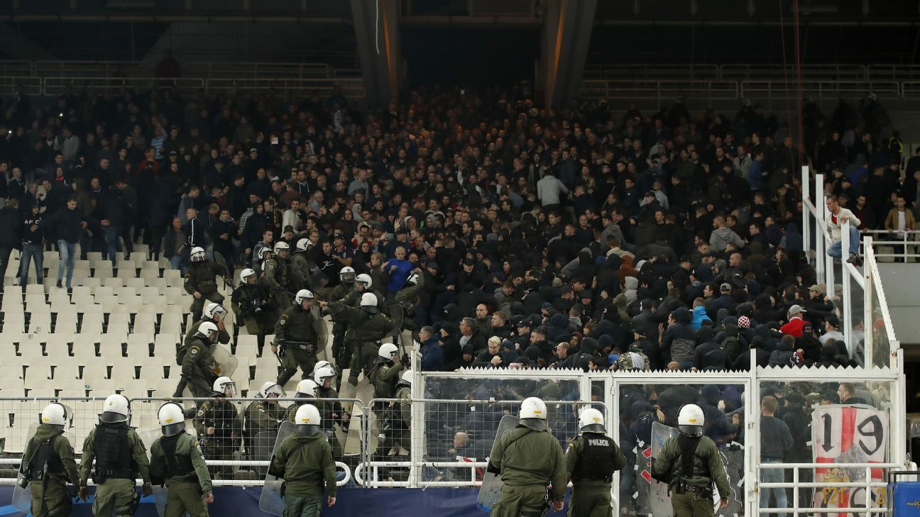 Riot police and Ajax supporters clash in the stands in Athens during Ajax's Champions League match with AEK Athens.