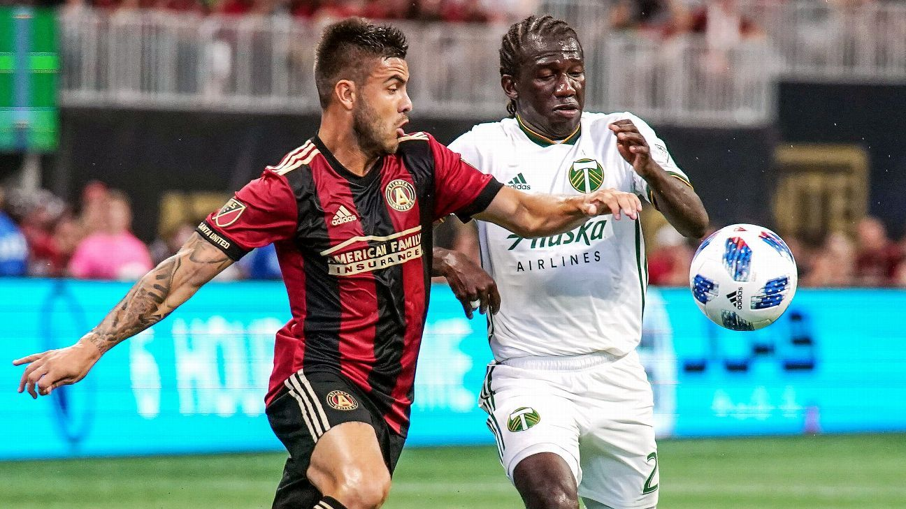 Hector Villalba and Diego Chara vie for the ball during Atlanta United's MLS match against the Portland Timbers.