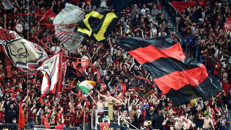 Atlanta United fans wave flags during the MLS Cup playoff match against New York City FC.