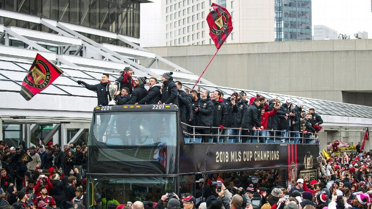 Atlanta United players ride an open-top bus at a parade celebrating the club's MLS Cup win.