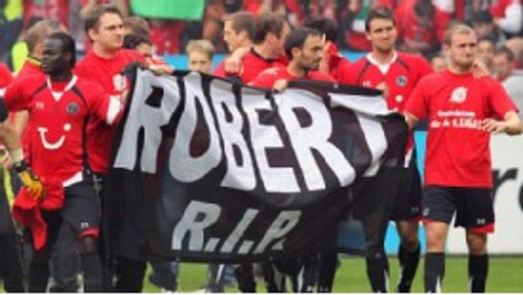 Hannover players display a banner in tribute to the late Robert Enke