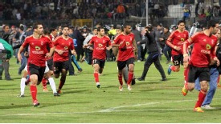 Al-Ahly players ran for safety as supporters invaded the pitch in Port Said, Egypt
