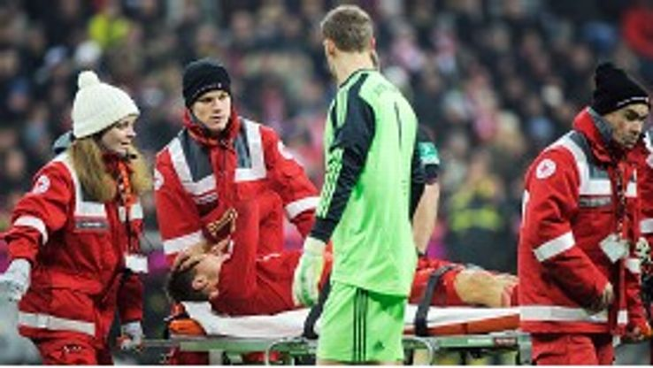 Manuel Neuer checks on Holger Badstuber as he is carried off injured against Dortmund