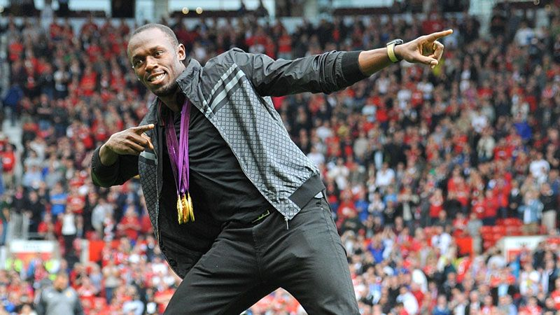 Bolt showing off his Olympic gold medals at Old Trafford