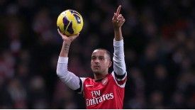 Theo Walcott celebrates with the match ball after his hat-trick helped Arsenal to a 7-3 victory
