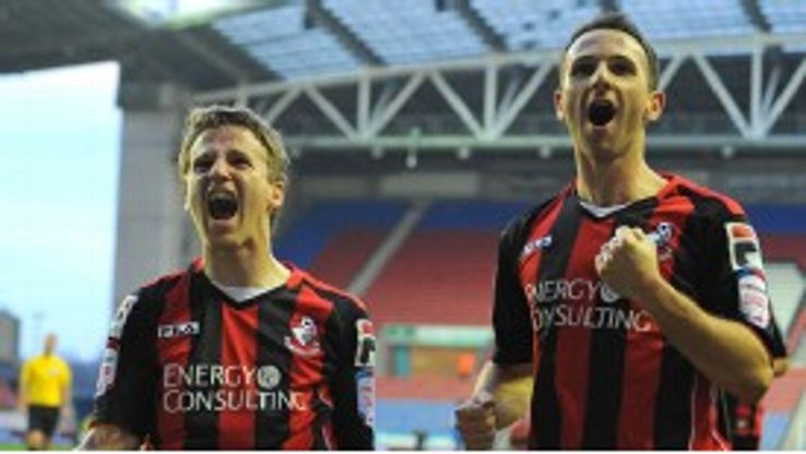 Eunan O'Kane (L) celebrates with Marc Pugh after putting Bournemouth ahead at Wigan