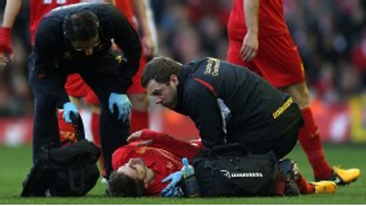 Liverpool's Fabio Borini gets treatment after injuring his shoulder
