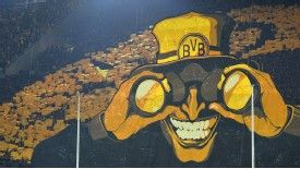 Dortmund fans wave their colours behind a giant poster ahead of the Champions League quarter-final with Malaga