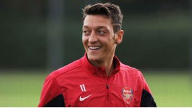 Ozil smiles during his first day of training at Arsenal.