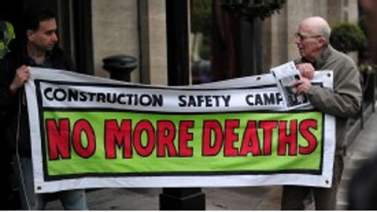 Protestors in London hold up a banner complaining about the abuse of workers in Qatar.