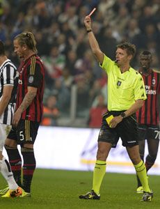Referee Gianluca Rocchi shows Philippe Mexes the red card during the defeat to Juventus.
