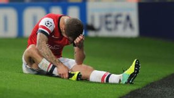Jack Wilshere clutches his ankle in the Champions League match against Dortmund.